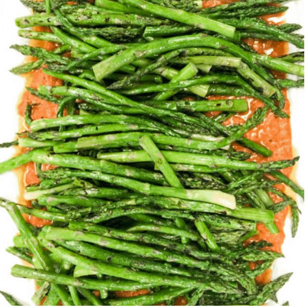 platter of asparagus on top of romesco sauce