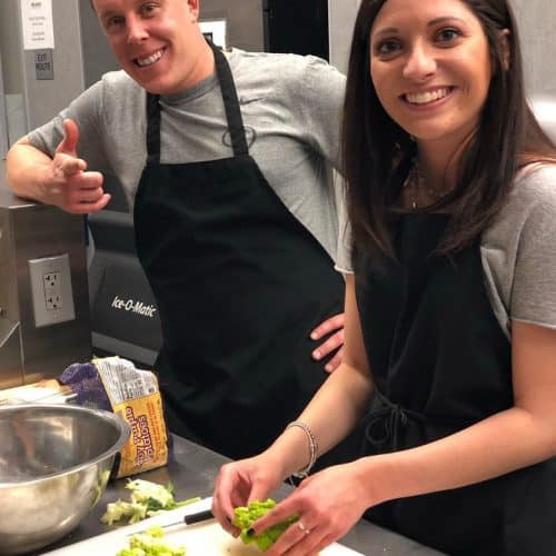 two guests cooking in the kitchen at a cooking party
