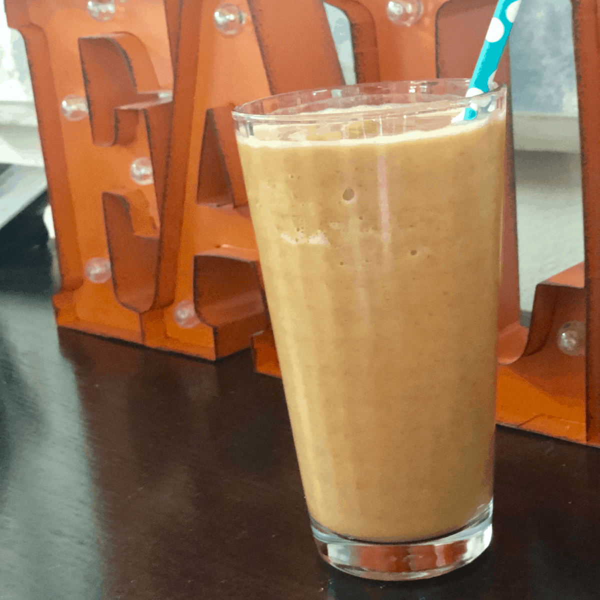 Glass filled with Pumpkin Spice Protein Shake in front of a fall sign.
